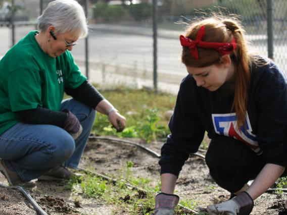 A UA student and a volunteer supervisor volunteering near campus